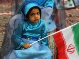 A young Iranian girl holds a national flag during a ceremony marking the 36th anniversary of the return from exile of the founder of Iran's Islamic Republic, Ayatollah Ruhollah Khomeini. PHOTO: AFP