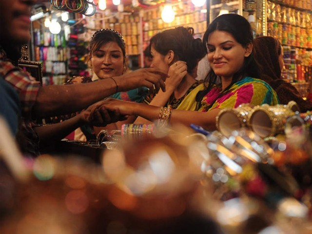 Pakistani Muslim women shop for bangles at a market in Karachi ahead of Eid ul Fitr. PHOTO: AFP