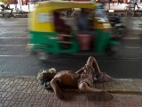 A homeless man takes a nap by the roadside under a metro station in New Delhi, India. PHOTO: AFP
