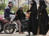 A woman speaks on the phone as men ride a motorcycle on a cloudy day n Riyadh. PHOTO: REUTERS