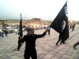An Islamic State group fighter brandishes an ISIS flag and a gun on a street in Mosul, Iraq, June 23, 2014. PHOTO: REUTERS