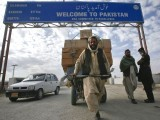 A Pashtun man passes a road sign while pulling supplies towards the Pakistan-Afghanistan border crossing. PHOTO: REUTERS