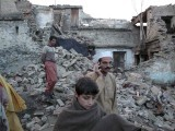 Residents walk past the rubble of a house after it was damaged by an earthquake in Mingora, Swat.  PHOTO: REUTERS