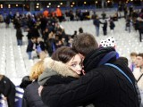 A supporter comforts a friend at the Stade de France stadium at the end of the international friendly soccer match. PHOTO: AP