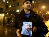 An activist holds a tablet with a picture of the lifeless body of a Russian pilot of a war plane shot down by Turkey, in front of the Turkish embassy in Moscow, Russia, November 24, 2015.  PHOTO: REUTERS