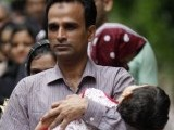 A Pakistani refugee who is a member of the Ahmadi, an Islamic minority sect, carries his daughter as he is released from a detention centre in Bangkok June 6, 2011.  PHOTO: REUTERS