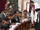 Christians take communion during a Christmas mass at a church in Quetta. PHOTO: AFP