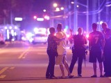 Orlando Police officers direct family members away from a multiple shooting at a nightclub. PHOTO: AP