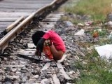 An Indian child defecates in an open near a railway track on. PHOTO: AFP