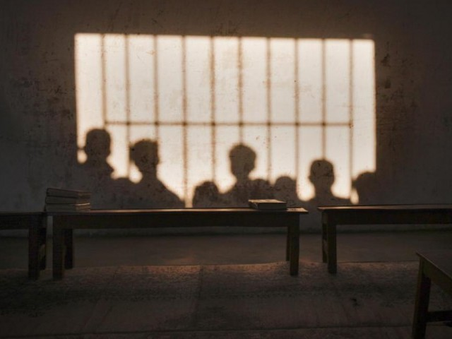 Copies of the Koran, Islam's holy book, sit on a bench as the shadows of boys, looking into the Zakariya madrassa, fall onto a classroom wall in Karachi
