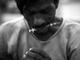 Heroin addict holds a syringe between his teeth after injecting heroin in the middle of a street near Kala Pull, Karachi. PHOTO: AFP