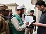 An official from the Pakistan Bureau of Statistics collects information from a resident during a census as security personnel guard them in Peshawar on March 15, 2017. PHOTO: AFP
