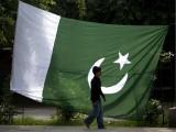 A boy walks past a Pakistani flag in Rawalpindi. PHOTO: REUTERS