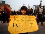 A Pakistani Shia Muslim girl holds placard during a protest against the twin bombings in Quetta, in Karachi, Pakistan on January 13, 2013. PHOTO: AFP