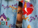 An autistic child peers from between curtains at the Consulting Centre for Autism in Amman, Jordan. PHOTO: REUTERS