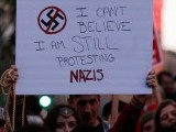A demonstrator holds signs during a rally in response to the Charlottesville, Virginia car attack on counter-protesters after the