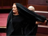 Australian One Nation party leader Senator Pauline Hanson pulls off a burka at Parliament House yesterday. PHOTO: REUTERS