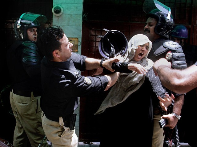 A police officer scuffles with a female protester during clashes in Lahore, Tuesday, June 17, 2014. PHOTO: AP