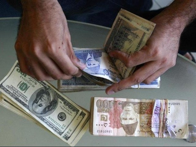 A currency dealer counts Pakistani rupees and U.S. dollars at his shop in Karachi. PHOTO: REUTERS