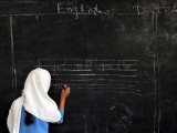 A Pakistani female student writes a sentence on a black board at a government school in Peshawar on October 25, 2012. PHOTO: AFP