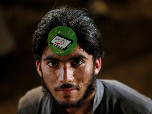 A supporter of the Muttahida Majlis-e-Amal (MMA) adorns an electoral sticker during a campaign rally, ahead of general elections in Karachi, Pakistan July 15, 2018. PHOTO: REUTERS