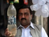 Mureed Abbas, field officer of Acid Survivors Foundation, holds a bottle of acid for sale at a shop for 40 Pakistan rupees. PHOTO: AFP