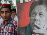 A supporter of Imran Khan's PTI party looks at the party leader's poster in Islamabad, July 2018. PHOTO: AFP