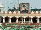 The portrait of Muhammad Ali Jinnah is displayed at the India-Pakistan border in Wagah as a Pakistani Ranger unfurls the flag during a ceremony to celebrate Pakistan's Independence. PHOTO: AFP