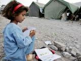 A Pakistani Kashmiri girl, a survivor of the 08 October 2005 earthquake, studies outside her makeshift tent in Muzaffarabad. PHOTO: AFP
