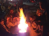 Shopkeepers in Quetta huddled together in front of a fire to escape the cold. PHOTO: SAADEQA KHAN