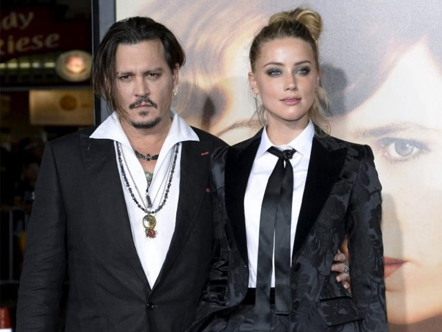 Cast member Amber Heard and husband Johnny Depp pose during the premiere of the film