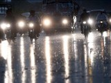Pakistani commuters travel on a street during heavy rain. PHOTO: GETTY