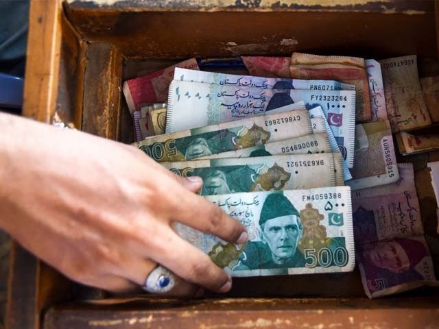 A Pakistani man counts Pakistan's rupees at his shop in Karachi. PHOTO: GETTY