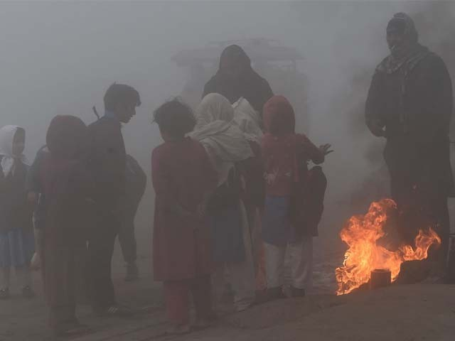 Pakistani school children stand around a wood fire as they wait for transport amid heavy smog. PHOTO: GETTY
