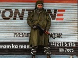 An Indian paramilitary trooper stands guard in front of closed shops during a lock-down in Srinagar. PHOTO: GETTY