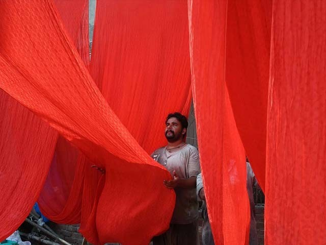 A labourer hangs fabrics to dry after a dyeing process in Lahore. PHOTO: GETTY