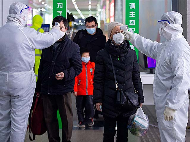Government workers check the temperature of travellers at the exit of a railway station in Nanjing.   PHOTO: GETTY