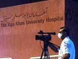 A cameraman wears a protective face masks as he films outside the Aga Khan University Hospital. PHOTO: GETTY