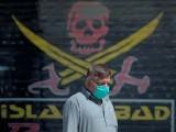 A Pakistani man wearing a face mask walks past closed market shops in Karachi. PHOTO: GETTY