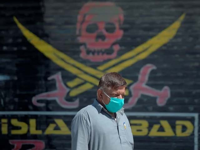 A Pakistani man wearing a face mask walks past closed market shops in Karachi. PHOTO: GETTY