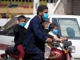 A man and his children adorn face masks as they ride a motorcycle during a government imposed lockdown.  PHOTO: GETTY
