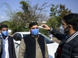 Men get checked for fever with a temperature gun. PHOTO AFP