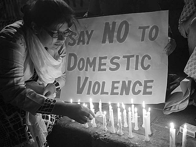A woman lights a candle at a protest against domestic violence. PHOTO: REUTERS