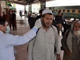 A health official checks the body temperature of a passenger at a railway station in Peshawar. PHOTO: GETTY