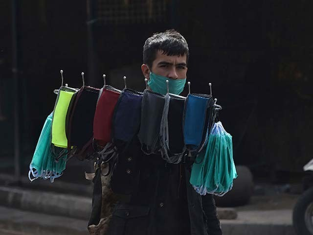 A vendor carries face masks for sale on a deserted street during a lockdown. PHOTO: GETTY