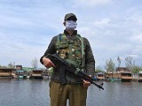 An Indian policeman wearing a face mask stands guard at Dal lake in Srinagar. PHOTO: GETTY