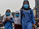 Students wear face masks on their way to school. PHOTO: GETTY