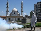 A worker wearing protective gear sprays disinfectant in Islamabad. PHOTO: GETTY