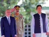 Visiting Afghan President Ashraf Ghani and Prime Minister Imran Khan review an honour guard. PHOTO: AFP