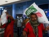 Porters get free essential food items at the Lahore railway station. PHOTO: AFP